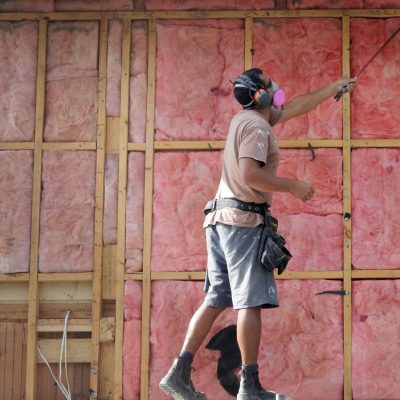 AUCKLAND - APR 18 2018:Builder removing old fiberglass wall insulation.Home improvement companies traded asbestos insulation for fiberglass after finding out the harmful effects asbestos has on lungs.